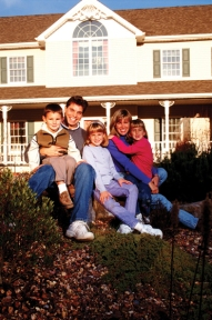 Family sitting in front of house, smiling